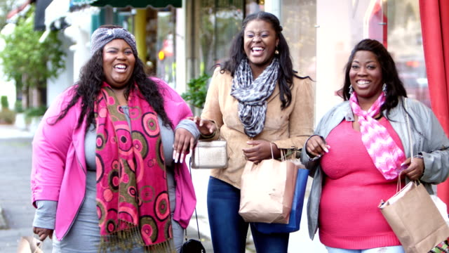 Three African-American women shopping in the city