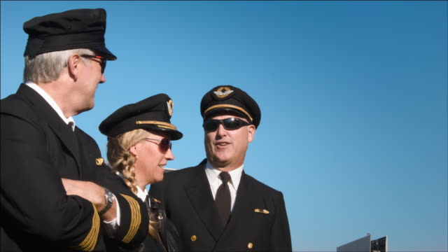 W/S three airline pilots watch as aircraft passes overhead: Singapore Airlines Airbus A340