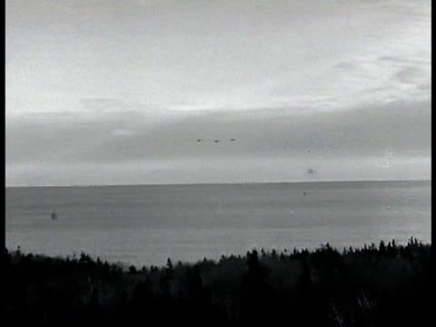 Three airplanes approaching evergreen tree lined harbor HA WS Ships anchored off harbor
