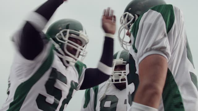 CU, LA, Three American football players in huddle, Staten Island, New York, USA