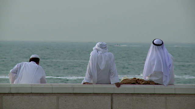 MS Three Arab men looking over Persian Gulf / Dubai, United Arab Emirates