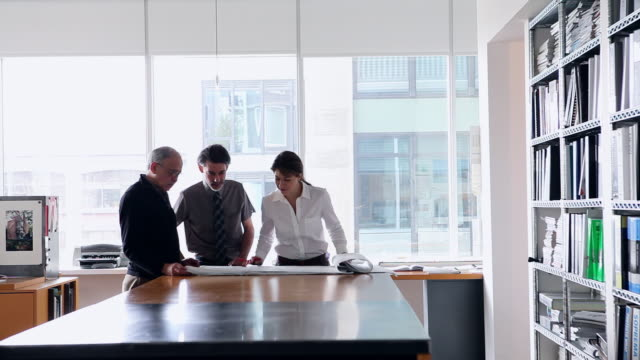 MS Three architects in office at desk examining plans/Seattle, Washington, USA