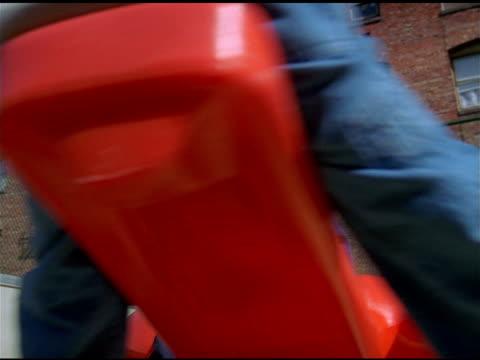 vídeos y material grabado en eventos de stock de three asian american children play on spinning red plastic plane in playground, brick building behind, san francisco - balancearse