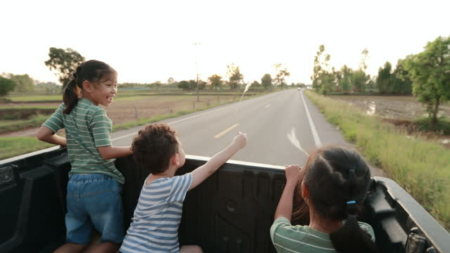 three asian siblings boy and girls sitting and playing together in a car trunk while traveling in the countryside with sunlight. - sitting stock videos & royalty-free footage