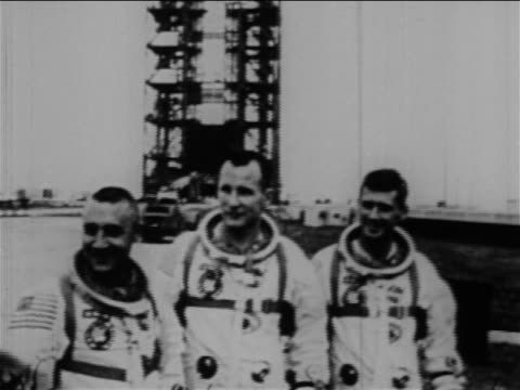 three astronauts in spacesuits posing outdoors with launch tower in background / apollo 1 - 宇宙服点の映像素材/bロール