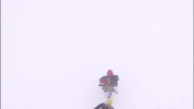 three backpackers struggle through deep snow as a blizzard rages. - blizzard stock videos & royalty-free footage