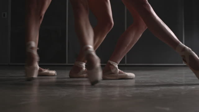 three ballerina's feet in point shoes moving in unison