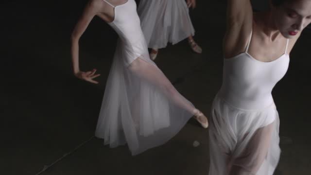 three ballerinas performing arabesque - auf einem bein stock-videos und b-roll-filmmaterial