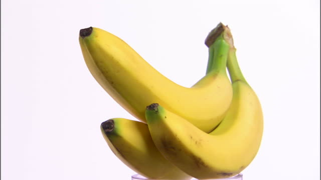 ms three bananas rotating against white background / orem, utah, usa - three objects stock videos & royalty-free footage