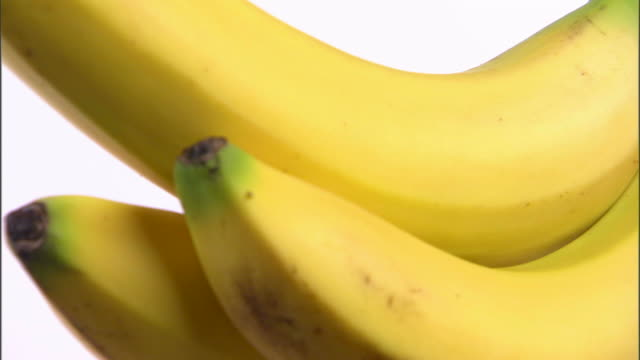 cu three bananas rotating against white background / orem, utah, usa - inquadratura dall'alto di un tavolo video stock e b–roll