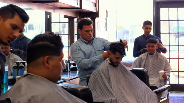 ms three barbers working on clients hair in barber shop - hair clipper stock videos & royalty-free footage