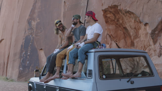 slo mo. three barefoot young men sit and talk on roof of vehicle by utah roadside on rock climbing expedition. - barefoot点の映像素材/bロール