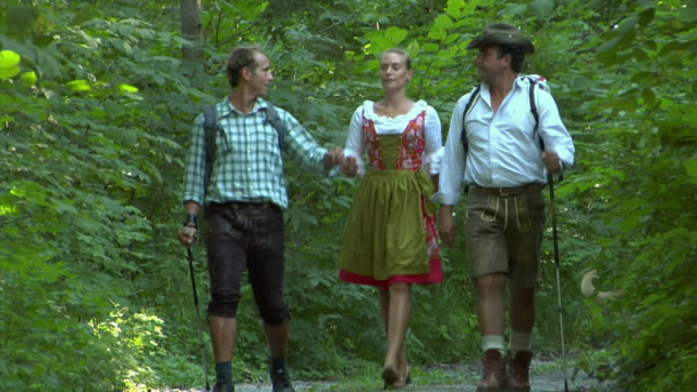 WS MS Three Bavarian people in traditional clothing hiking through forest, Bavaria, Germany