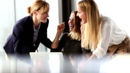 Three beautiful business woman cheering and high-fiving in office meeting