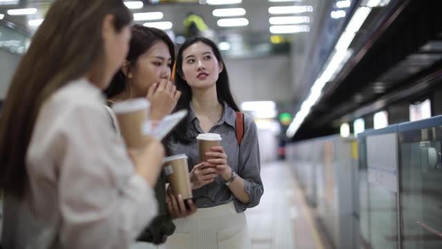 地下鉄の駅に立っている3人の美しい女性の友人 - 路面電車点の映像素材/bロール