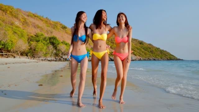 3美しい女の子が歩いて、ビーチで楽しんでいます。休暇-istock - 水着点の映像素材/bロール