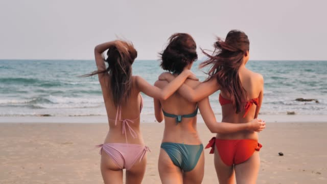 Three beautiful girls walking in a summer day having fun on the beach,Group of young women on the beach in small sexy bikinis,vacation having fun.Vacations - iStock