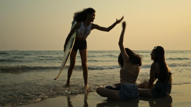 美しい空の間にビーチで楽しく海の中で遊んで3人の美しい女性。 - 水着点の映像素材/bロール