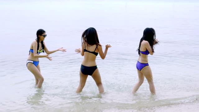 vídeos y material grabado en eventos de stock de tres hermosas mujeres jóvenes felices en bikini disfrutando de sus vacaciones en la playa - bronceado