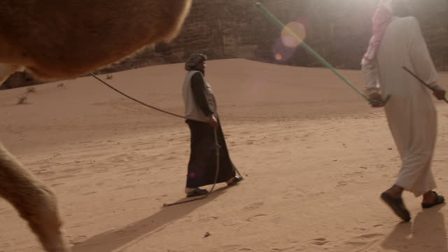 three bedouin men lead camels in jordan - camel train stock videos & royalty-free footage
