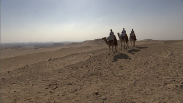 three bedouins on camels gaze at the pyramids before riding across the desert toward the pyramids. - ベドウィン族点の映像素材/bロール