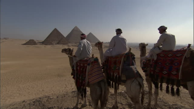 three bedouins on camels stop to gaze at pyramids and then ride on. - ベドウィン族点の映像素材/bロール