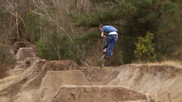 ws pan three bmx rider jumping over dirt mounds and falls off bike at last hill  / jacksonville, florida, usa - un ragazzo adolescente video stock e b–roll