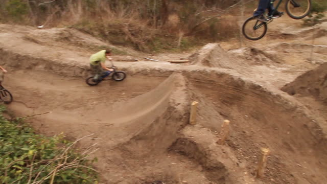 ws pan three bmx riders jumping over dirt mounds / jacksonville, florida, usa - bmx cycling stock videos and b-roll footage