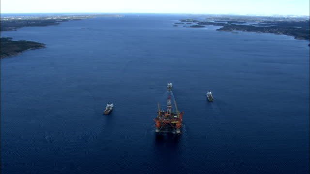 three boats moored around an oil drilling rig off the coast of norway. available in hd. - oil rig boat stock videos & royalty-free footage