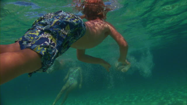 SLO MO, MS, Three boys (6-7, 8-9, 14-15) and woman diving in ocean waves, Oahu's North Shore, Hawaii, USA