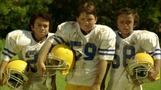 CU, Three boys (6-7) in football gear on field, portrait