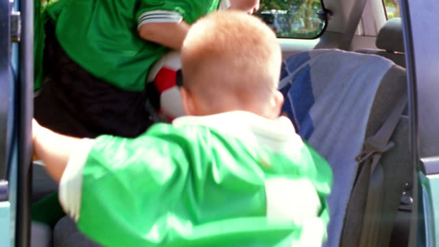 CANTED MS three boys in soccer uniforms entering minivan + fastening seat belts / Florida