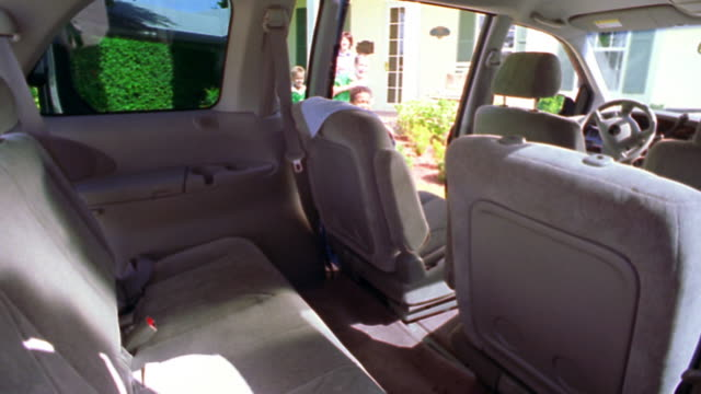 MS three boys in soccer uniforms with soccer balls entering minivan with woman following / Florida