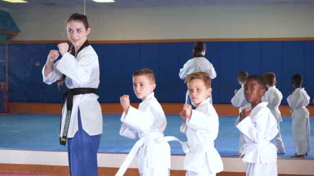 three boys in taekwondo class with instructor - bow pose stock videos & royalty-free footage