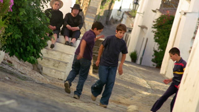 Three boys kick soccer ball in village street / people watch on side of street / Monsaraz, Portugal