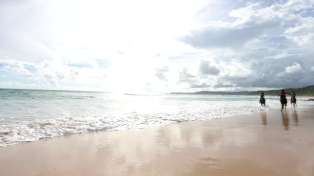 vidéos et rushes de three boys on horseback galloping along beach towards camera along water's edge and splashing past - monter sur un moyen de transport