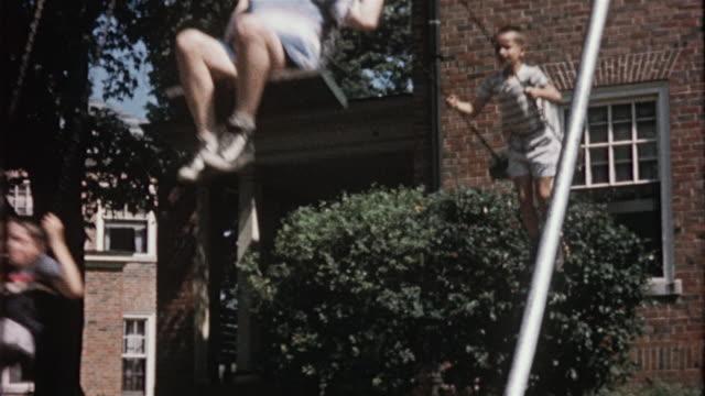 vídeos y material grabado en eventos de stock de 1956 ms three boys on swing set / usa - columpiarse