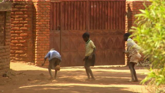 WS, Three boys (8-9) playing soccer in street, Lilongwe, Malawi