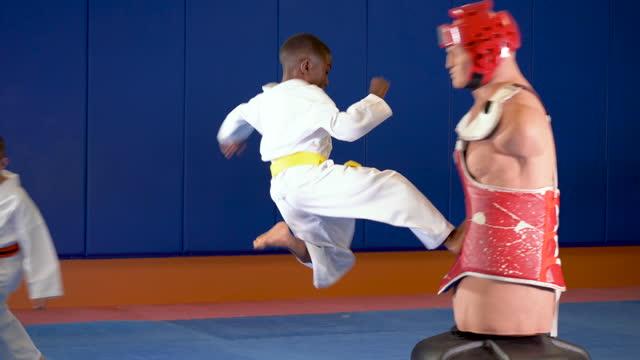 stockvideo's en b-roll-footage met drie jongens die taekwondo op dummy praktizeren - driekwartlengte
