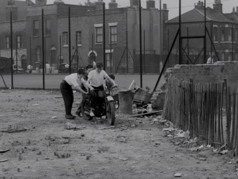 three boys push another boy on a motorcycle across the grounds of a youth club. 1957. - youth club stock videos & royalty-free footage