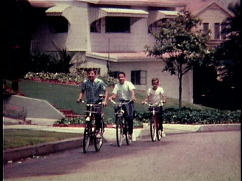 ws pan three boys riding bicycles down suburban street / usa - 郷愁点の映像素材/bロール