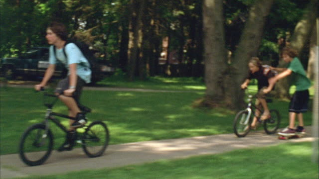 ws ts pan three boys riding bikes and skateboarding down suburban sidewalk / cazenovia, new york, usa - bicycle stock videos & royalty-free footage