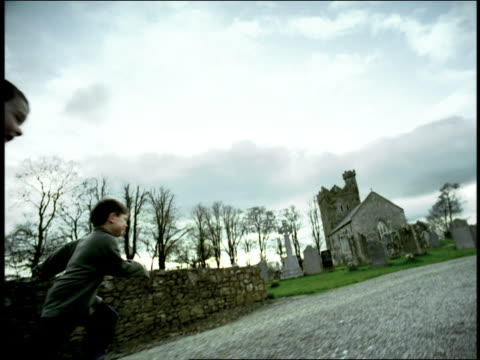 vidéos et rushes de high contrast rear view three boys running on country road past church + cemetery / ireland - pierre tombale