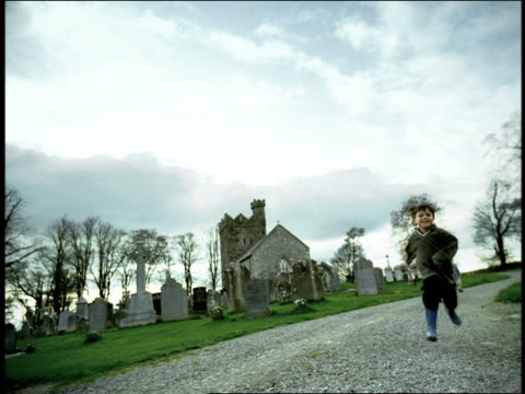 vídeos de stock, filmes e b-roll de high contrast three boys running on country road toward camera / church + cemetery in background / ireland - superexposto