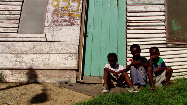 three boys sit in front of a shack in south africa. - poor family stock videos & royalty-free footage