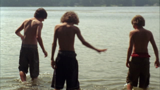 vídeos de stock, filmes e b-roll de cu tu pan ms three boys wading, splashing and pushing each other in lake / cazenovia, new york, usa - vadear