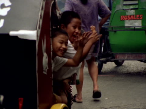 Three boys wave from a pedicab.