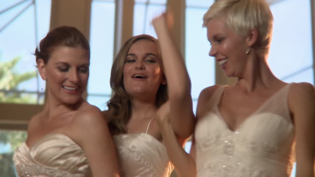 MS R/F Three brides dancing and showing off wedding ring / Jacksonville, Florida, USA
