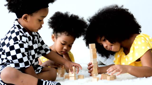vídeos de stock, filmes e b-roll de três irmãos e irmãs que jogam brinquedos - sala de estar