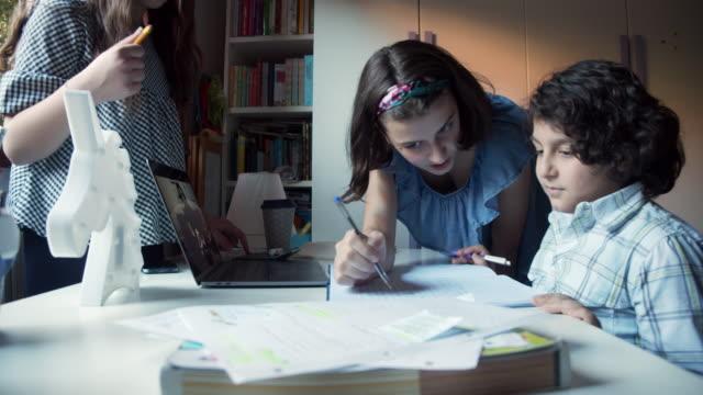 stockvideo's en b-roll-footage met drie broers die samen thuis bestuderen - 14 15 jaar